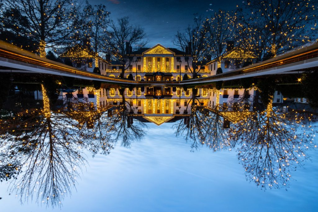 reflection of holiday lit building in pond at night